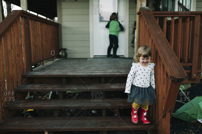 Girl standing on porch steps crying