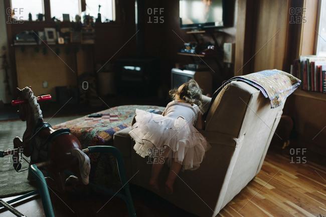 Girl in tutu climbing on living room chair