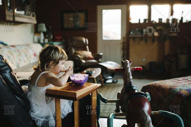 Girl in tutu eating in the living room