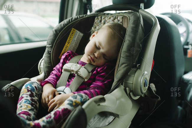 Young toddler fast asleep in car seat