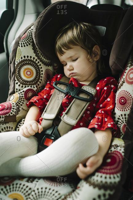 Young girl fast asleep in car seat