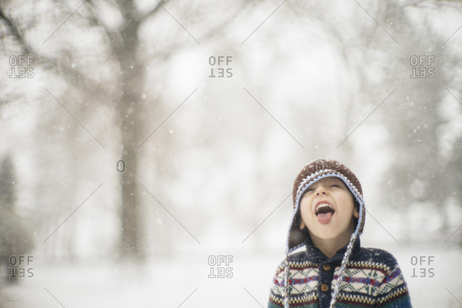 Boy catching snowflakes on tongue in yard