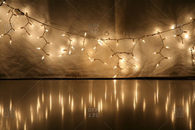 Christmas lights by tablecloth over shiny floor