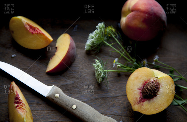 Peaches on wooden surface with a knife