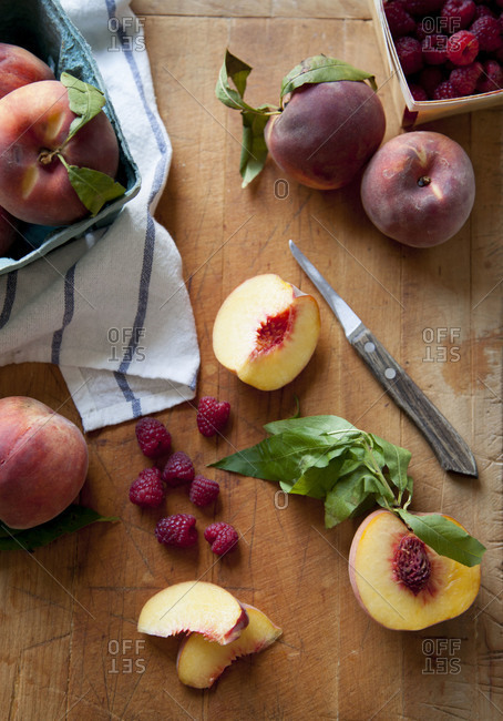Peaches and raspberries on a cutting board