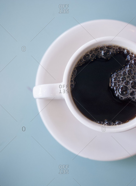 A white cup full of coffee on a white saucer