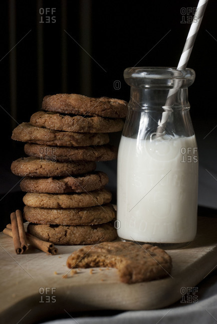 A tall stack of cookies next to a milk jar with a straw in it