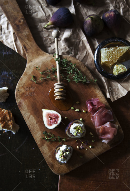 Sliced figs, bread and prosciutto on a cutting board