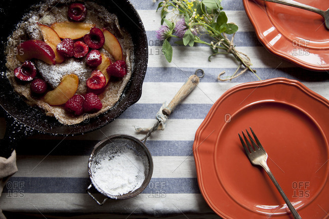 Pancake in a cast iron skillet on a blue and white striped cloth with pink plates