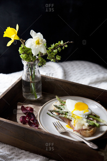 Open faced sandwich and vase of flowers on a wooden tray on a bed