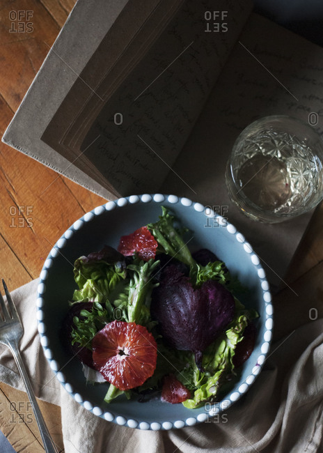 A salad with beets and blood oranges next to a book