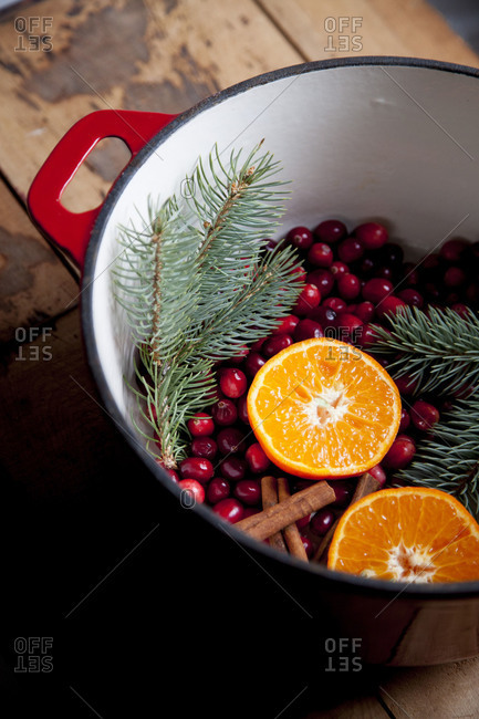 Pine branch, oranges, cranberries and cinnamon sticks in a pot