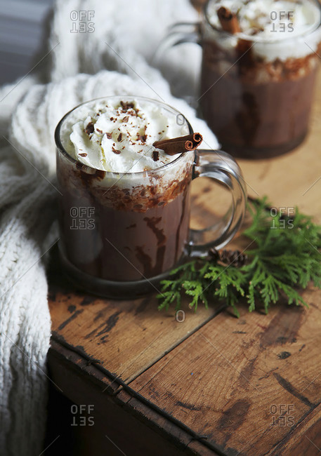Hot chocolate with whipped cream on a wooden background with blanket