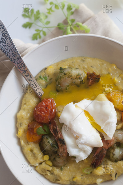 Polenta in a bowl with roasted tomatoes and a poached egg on a white background
