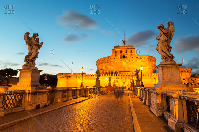 Rome, Lazio, Italy - May 26, 2014: Angel statues on Ponte Sant' Angelo bridge with Castel Sant' Angelo at dusk