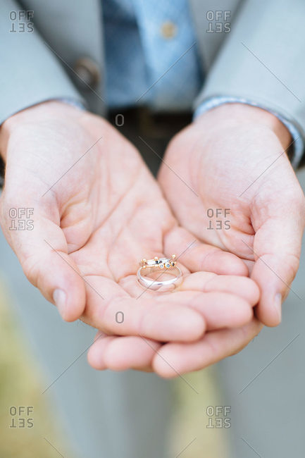 A man holds two wedding rings