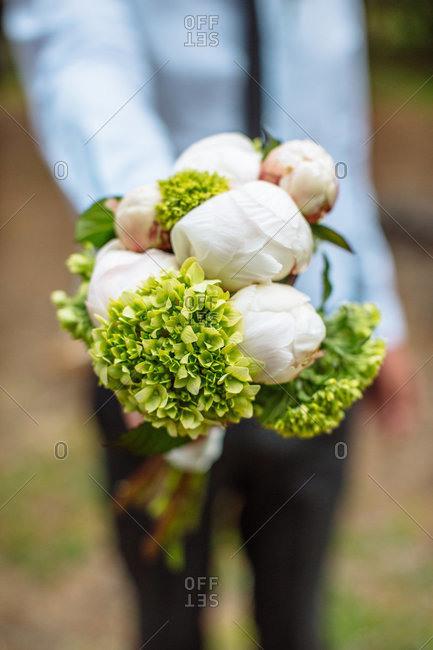 A man offers a bouquet of flowers