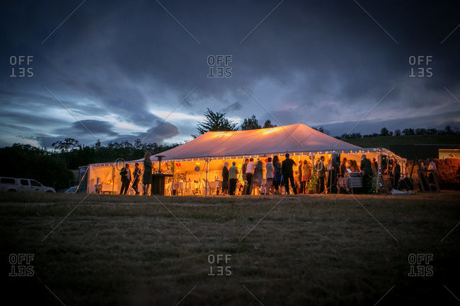 Wedding guests gather in a tent at the reception