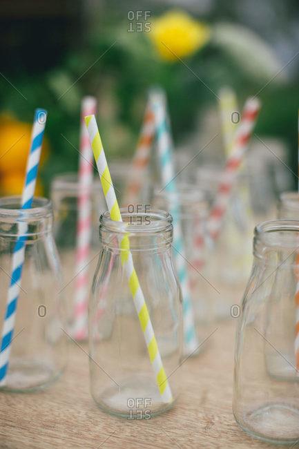 Colorful striped straws in milk jugs