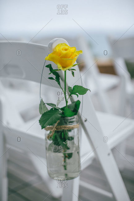 A yellow rose hangs in a mason jar on the end of a chair