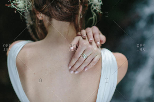 A bride reaches over her shoulder