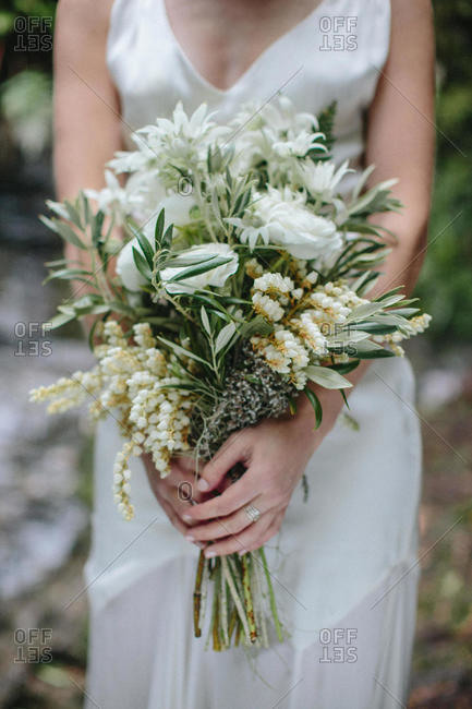 A bride holds a bouquet of fresh flowers