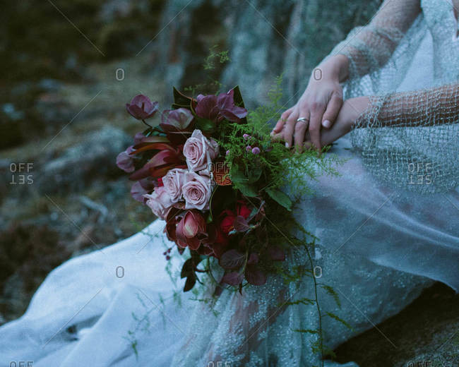 A bride sits outside in nature