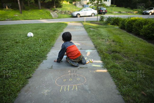 A boy creates chalk drawings on the sidewalk
