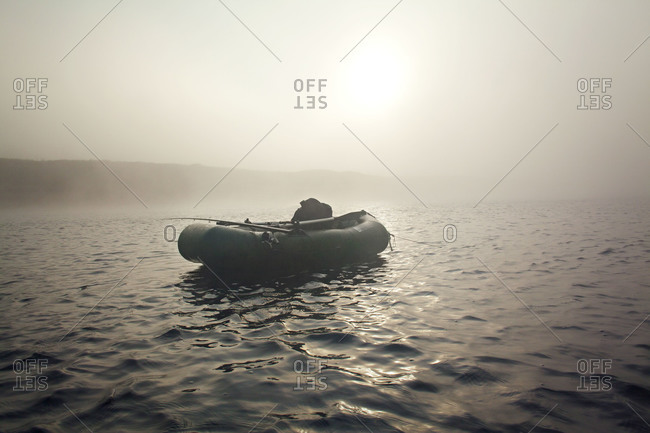 Inflatable fishing raft floating on a misty river