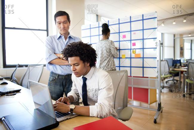 Boss looking over employee's shoulder in an office