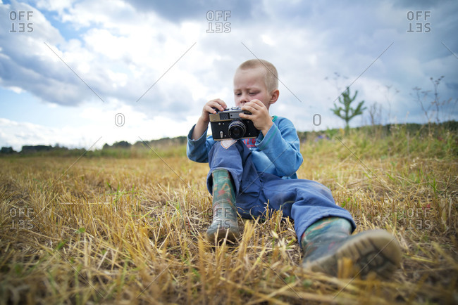 Young Boy Playing with Vintage Camera in a Field