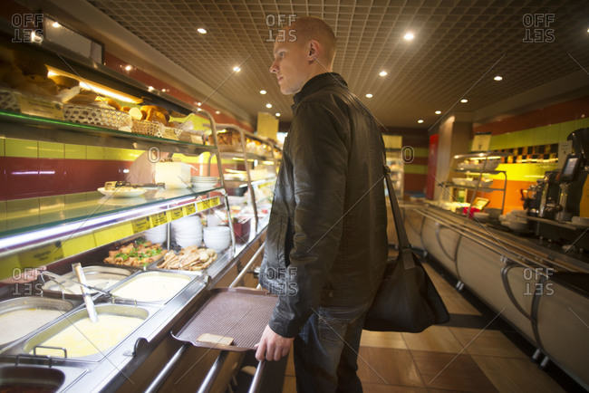 Man Choosing Food from Cafeteria Buffet