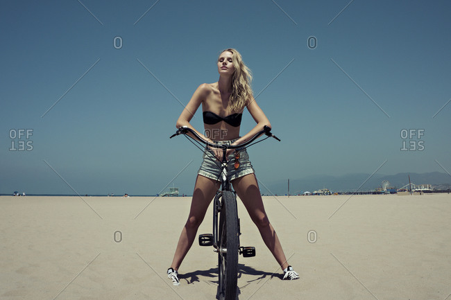 A woman on a bike at the beach
