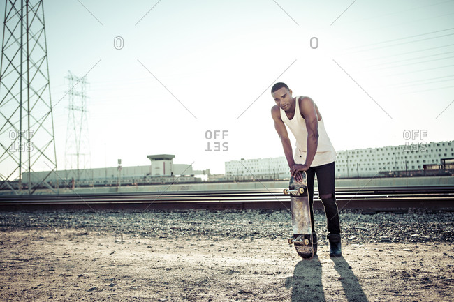 A skateboarder stands in front of railroad tracks