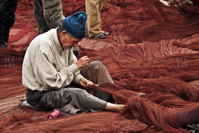 Essaouira, Morocco - August 10, 2010: Man repairing fishing net in Morocco