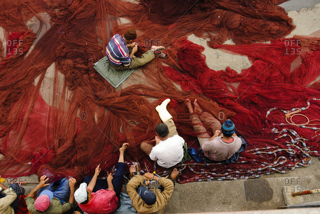 Men repairing fishing net in Morocco