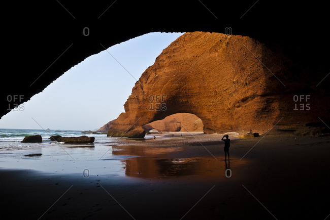 Person walking along rock arches on Moroccan beach