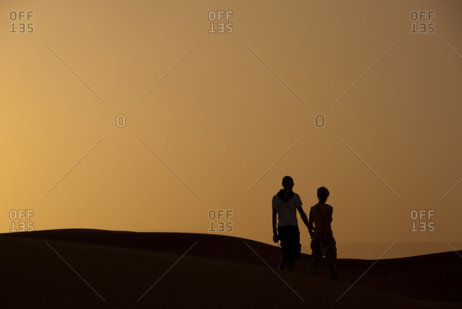 Couple exploring Moroccan dunes at sunset