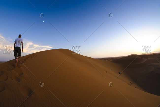 Man walking alone Moroccan sand dune