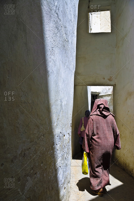 Woman walking in passageway in Fez, Morocco