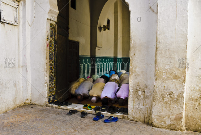 Men praying in mosque in Fez, Morocco