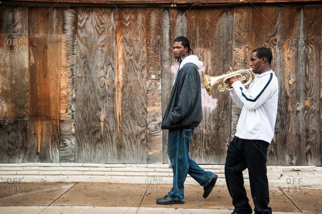 Two men walk along the sidewalk in the Treme neighborhood of New Orleans