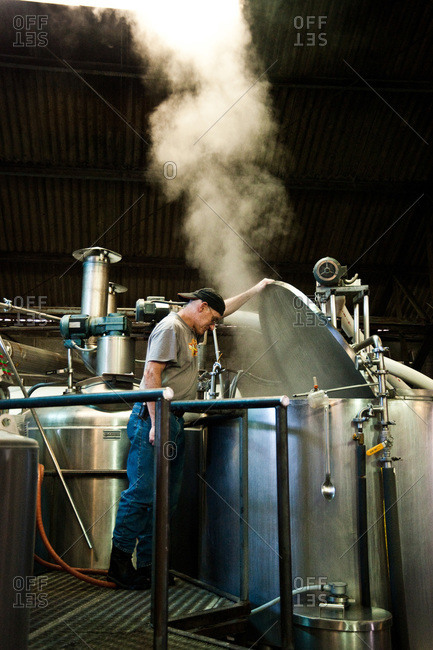A worker checks on a brewing tank at a New Orleans brewery