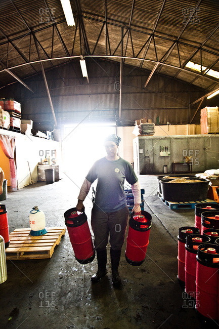 A worker carries liquid containers at a New Orleans brewery