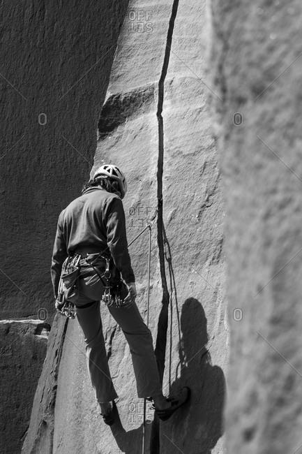 Indian Creek, Oregon, USA - March 25, 2014: Person pausing while rock climbing in Utah