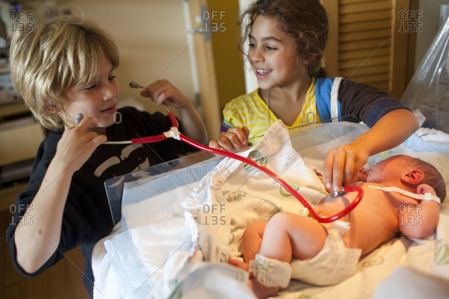 Siblings listening to the heartbeat of newborn in hospital