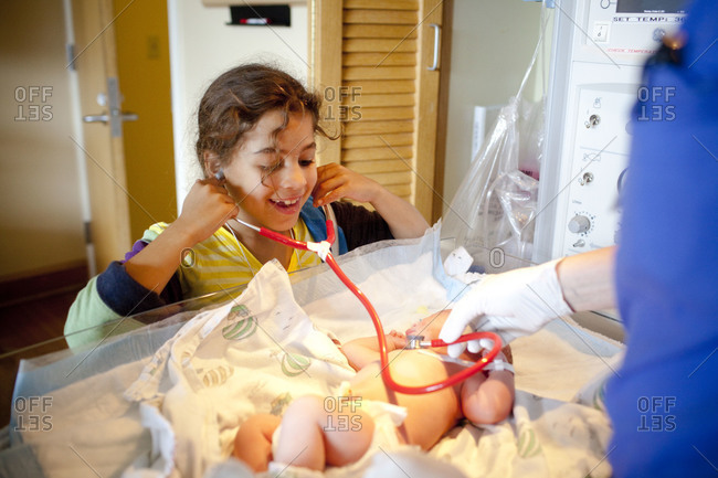 Sibling listening to the heartbeat of a newborn