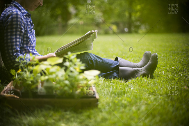 Gardener reading newspaper in garden