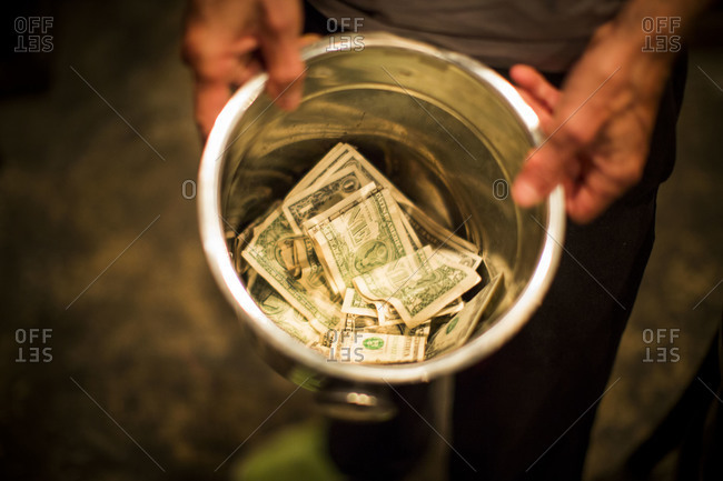 Beggar holding metal bucket with dollar bills