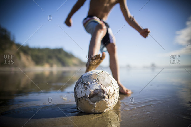 Young boy playing soccer on a beach